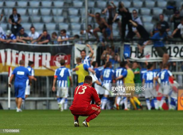Simon Stadler of FC Bayern Muenchen U19 looks dejected as Hansa Rostock players celebrate their second goal during the A Juniors championship first...