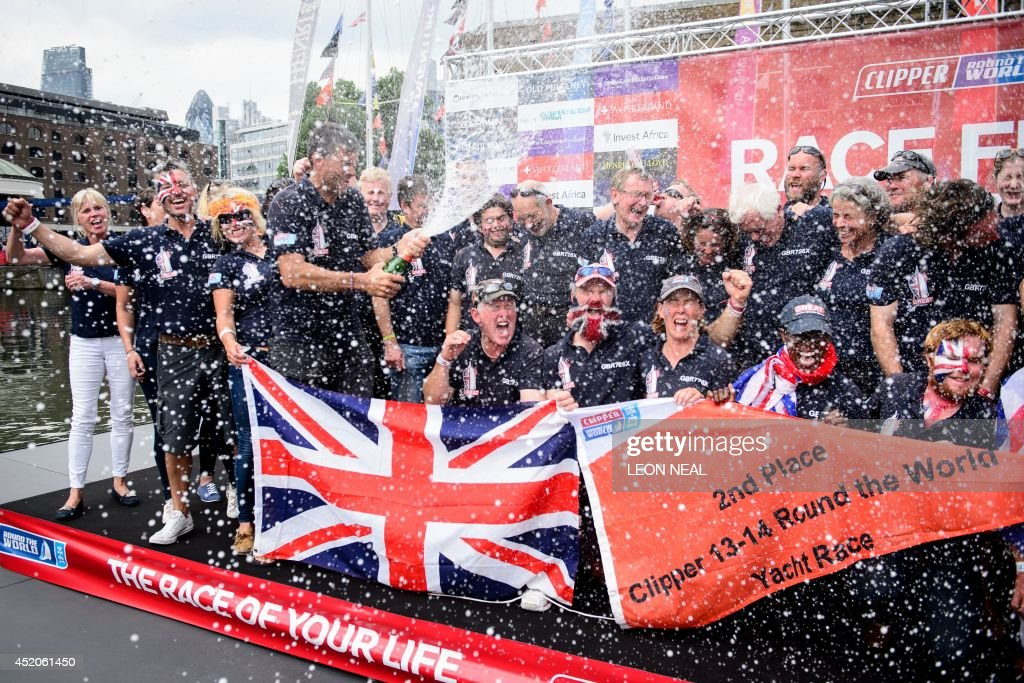 Simon Talbot (4-L), the skipper of the Great Britain yacht, sprays champagne over his crew in Saint Katherine's Dock in London, England after taking the second position in the 2013-14 Clipper Round the World Yacht Race, on July 12, 2014. The world's longest ocean race began on September 1, 2013, with a 12-strong fleet visiting 14 ports on six continents and travelling 40,000 miles before returning to the British capital. AFP PHOTO/Leon Neal
