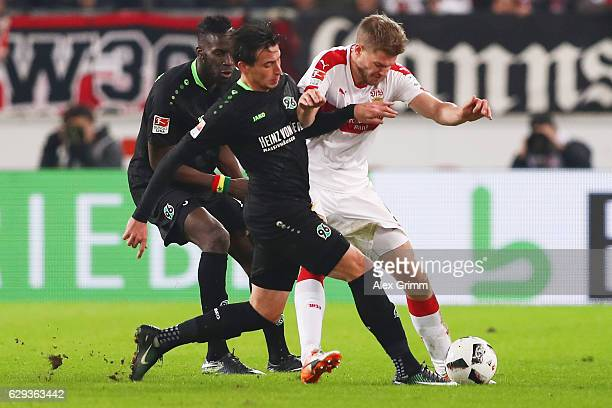 Simon Terodde of Stuttgart is challenged by Edgar Prib and Salif Sane of Hannover during the Second Bundesliga match between VfB Stuttgart and...