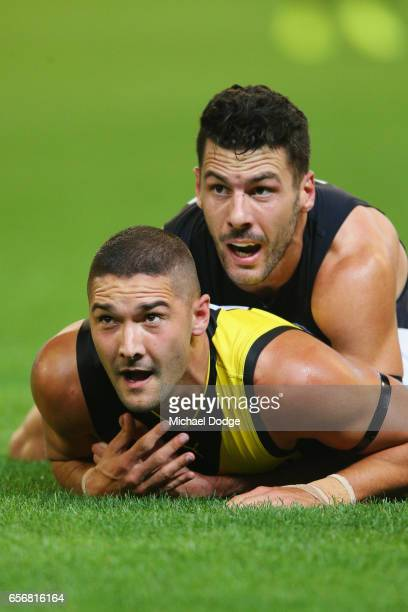 Simon White of the Blues tackles Shaun Grigg of the Tigers during the round one AFL match between the Carlton Blues and the Richmond Tigers at...