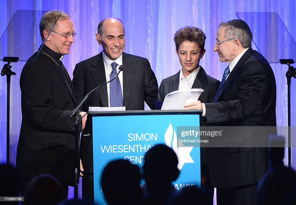 Simon Wiesenthal Center Founder Rabbi Marvin Hier (R) presents the Medal of Valor to Father Norbert Hofmann (L) accompanied by Lamberto Piperno (2nd L) and his son Ariel at the Simon Wiesenthal Center National Tribute Dinner at Regent Beverly Wilshire Hotel on June 11, 2013 in Beverly Hills, California.