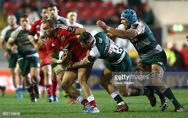 Simon Zebo of Munster is held by Adam Thompstone and Graham Kitchener during the European Rugby Champions Cup match between Leicester Tigers and...