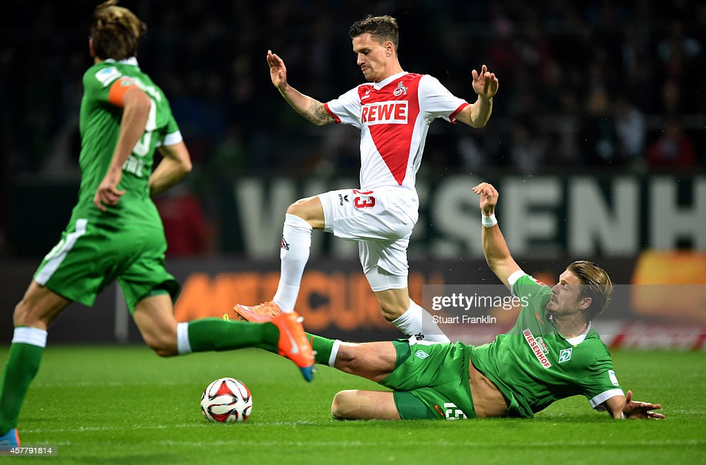 Simon Zoller of Koeln is tackled by Sebastian Prodl of Werder Bremen during the Bundesliga match between SV Werder Bremen and FC Koeln at...