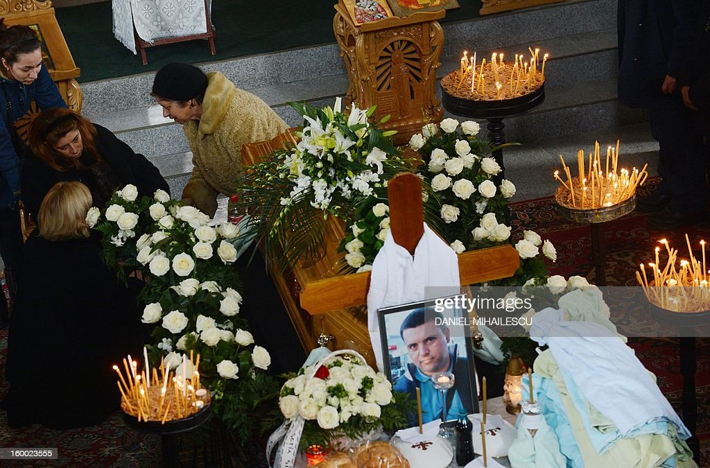 Simona Costache (2nd L) cries next to the coffin of her husband Tiberiu Ionut Costache, 36, one of the two Romanian victims who were killed during the Algerian hostage crisis, at the Orthodox church in Barcanesti village (50km north of Bucharest), January 24, 2012. Three other Romanians escaped the audacious attack by Islamist militants on a gas plant in the Algerian desert.