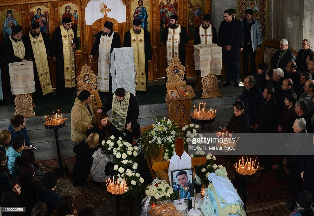 Simona Costache (C, L) cries next to the coffin of her husband Tiberiu Ionut Costache, 36, one of the two Romanian victims who were killed during the Algerian hostage crisis, at the Orthodox church in Barcanesti village (50km north of Bucharest), January 24, 2012. Three other Romanians escaped the audacious attack by Islamist militants on a gas plant in the Algerian desert.