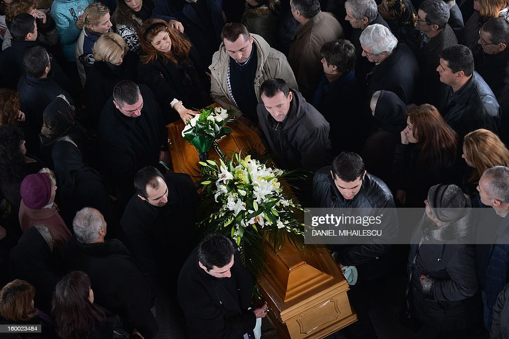 Simona Costache (top, L) touches the coffin of her husband Tiberiu Ionut Costache, 36, one of the two Romanian victims who were killed during the Algerian hostage crisis, at the Orthodox church in Barcanesti village (50km north of Bucharest), January 24, 2012. Three other Romanians escaped the audacious attack by Islamist militants on a gas plant in the Algerian desert. AFP PHOTO / DANIEL MIHAILESCU