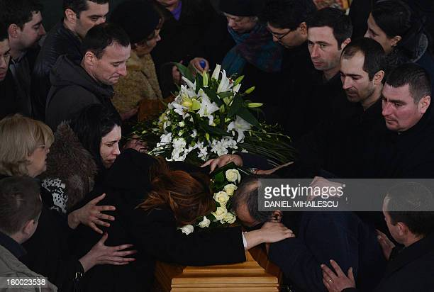 Simona Costache touches the coffin of her husband Tiberiu Ionut Costache one of the two Romanian victims who were killed during the Algerian hostage...
