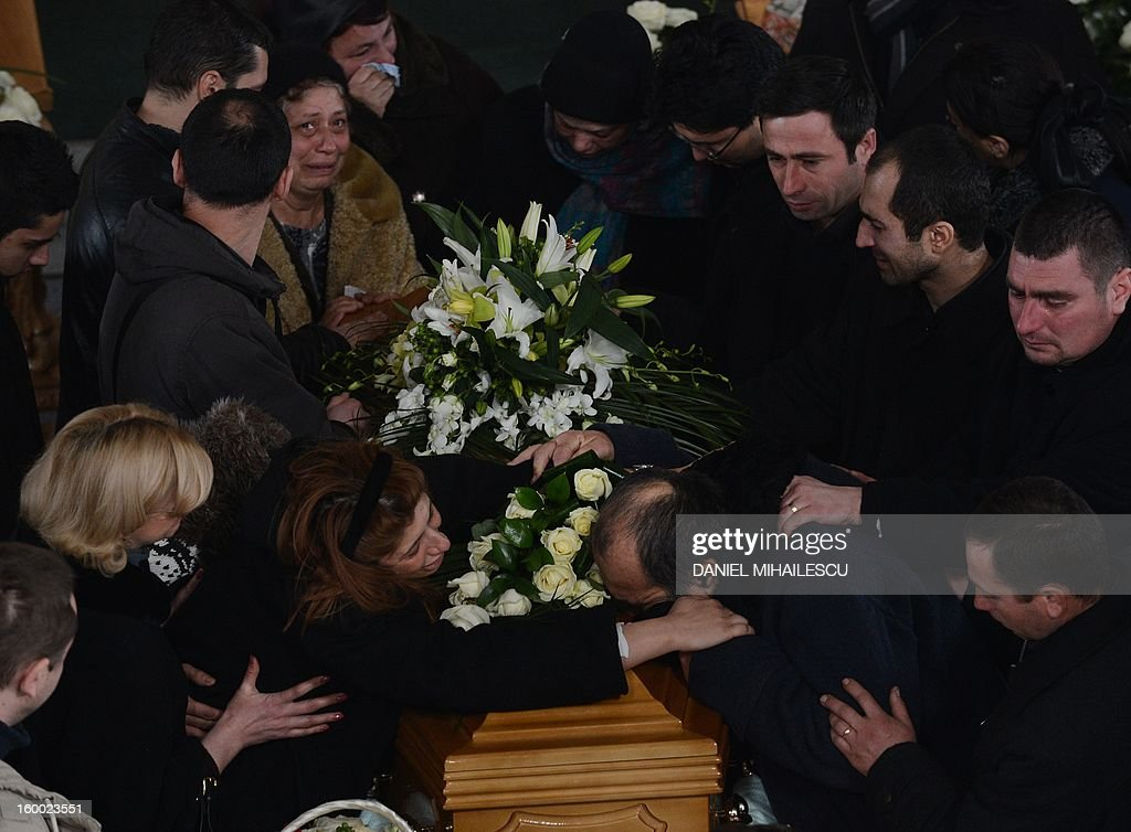 Simona Costache (L) touches the coffin of her husband Tiberiu Ionut Costache, 36, one of the two Romanian victims who were killed during the Algerian hostage crisis, at the Orthodox church in Barcanesti village (50km north of Bucharest), January 24, 2012. Three other Romanians escaped the audacious attack by Islamist militants on a gas plant in the Algerian desert. AFP PHOTO / DANIEL MIHAILESCU