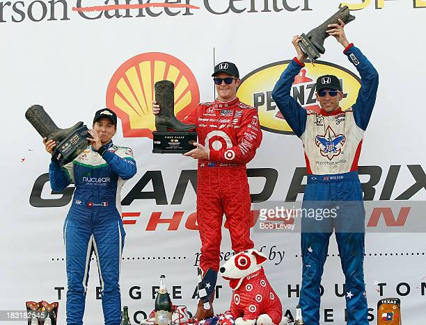 Simona De Silvestro Scott Dixon and Justin Wilson from left hold up their trophies during the IZOD IndyCar Series Shell and Pennzoil Grand Prix Race...