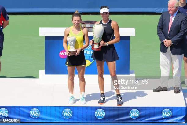 Simona Halep and Garbine Muguruza hold their trophies after their championship match at the Western Southern Open at the Lindner Family Tennis Center...