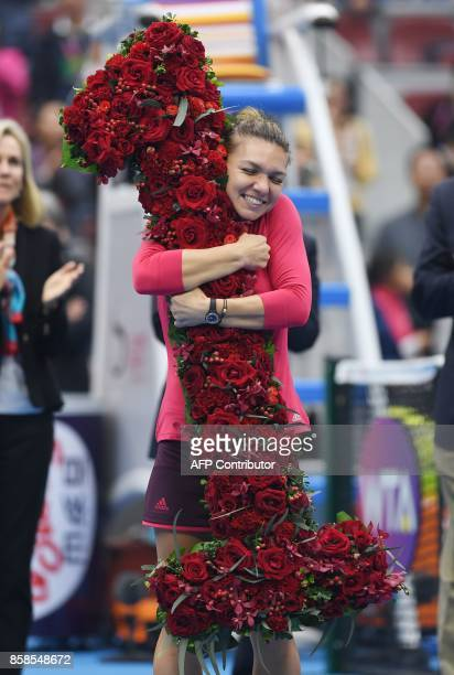 Simona Halep of Romania celebrates after being presented with a bouquet in the shape of the number '1' after taking the top ranking by winning her...