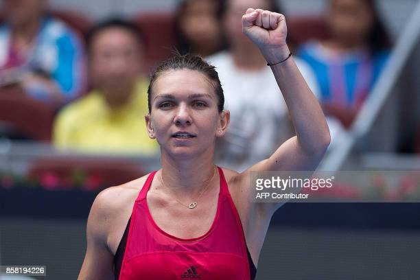 Simona Halep of Romania celebrates winning her women's singles quarterfinal match against Daria Kasatkina of Russia at the China Open tennis...