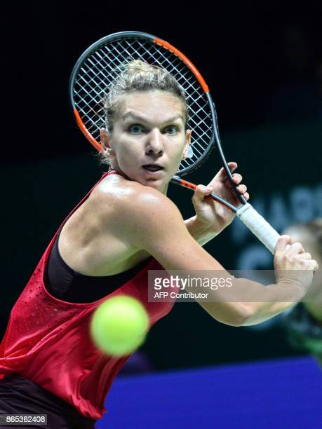 Simona Halep of Romania hits a return against Caroline Garcia of France during the WTA Finals tennis tournament in Singapore on October 23 2017 / AFP...