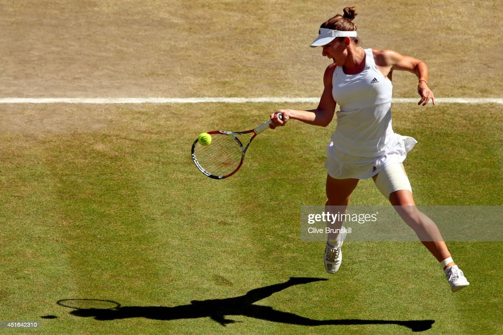 Simona Halep of Romania leaps to play a forehand return during her Ladies' Singles semifinal match against Eugenie Bouchard of Canada on day ten of...