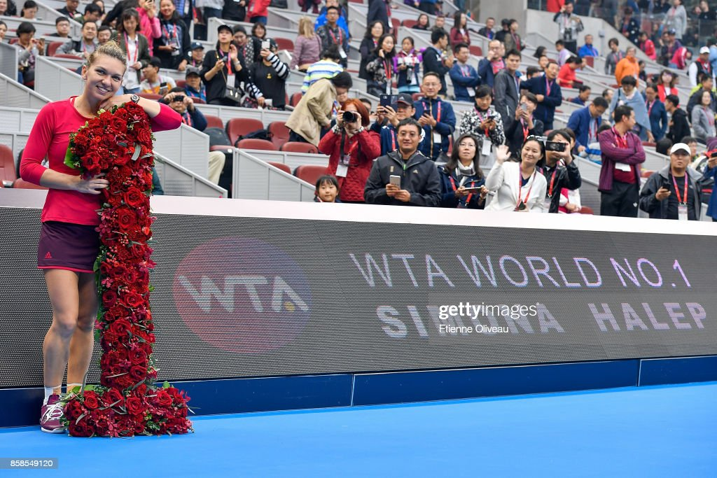 Simona Halep of Romania poses with flowers in front of a board displaying her name while she becomes world number one of the WTA rankings after her Women's single semifinal match against Jelena Ostapenko of Latvia on day eight of the 2017 China Open at the China National Tennis Centre on October 7, 2017 in Beijing, China.