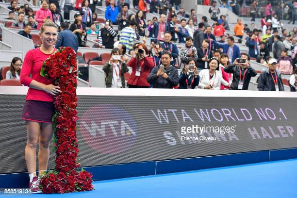 Simona Halep of Romania poses with flowers in front of a board displaying her name while she becomes world number one of the WTA rankings after her...