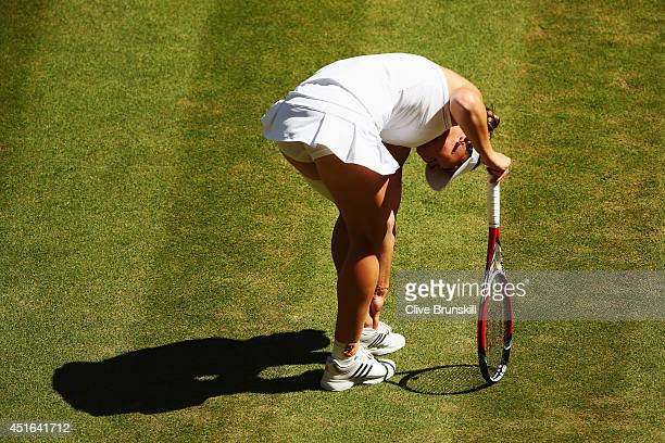Simona Halep of Romania reacts after sustaning an ankle injury during her Ladies' Singles semifinal match against Eugenie Bouchard of Canada on day...