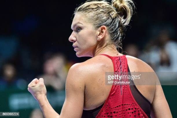 Simona Halep of Romania reacts on a point against Caroline Garcia of France during the WTA Finals tennis tournament in Singapore on October 23 2017 /...