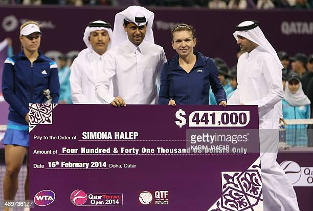 Simona Halep of Romania receives the winner's cheque from Nasser alKhelaifi president of the Qatar Tennis Federation after winning the Qatar Open...