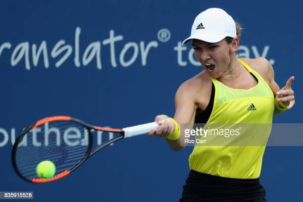 Simona Halep of Romania returns a shot to Garbine Muguruza of Spain during Day 9 of the finals of the Western and Southern Open at the Linder Family...