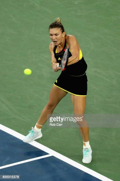 Simona Halep of Romania returns a shot to Johanna Konta of Great Britain during Day 7 of the Western and Southern Open at the Linder Family Tennis...