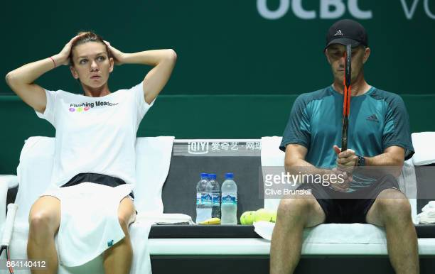 Simona Halep of Romania sits with coach Darren Cahill during practice prior to the BNP Paribas WTA Finals Singapore presented by SC Global at...