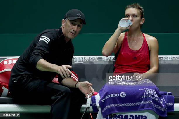 Simona Halep of Romania sits with coach Darren Cahill in her singles match against Caroline Garcia of France during day 2 of the BNP Paribas WTA...