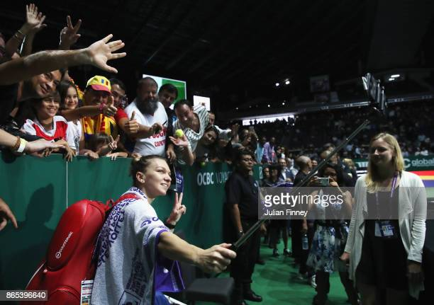 Simona Halep of Romania takes a selfie with fans after her singles match against Caroline Garcia of France during day 2 of the BNP Paribas WTA Finals...