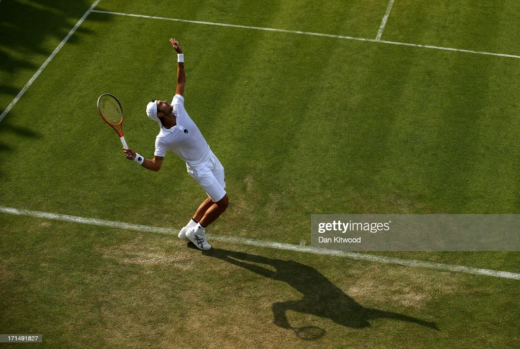 Simone Bolelli of Italy serves during his Gentlemen's Singles first round match against Grigor Dimitrov of Bulgaria on day two of the Wimbledon Lawn Tennis Championships at the All England Lawn Tennis and Croquet Club on June 25, 2013 in London, England.