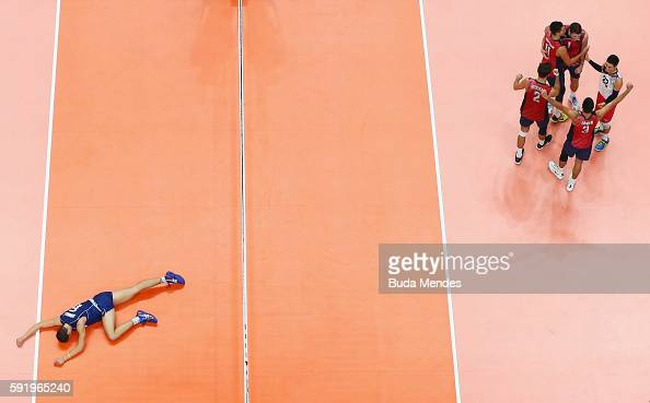 Simone Giannelli of Italy lies on the ground looking dejected as the United States celebrate a point during the Men's Volleyball Semifinal match on...