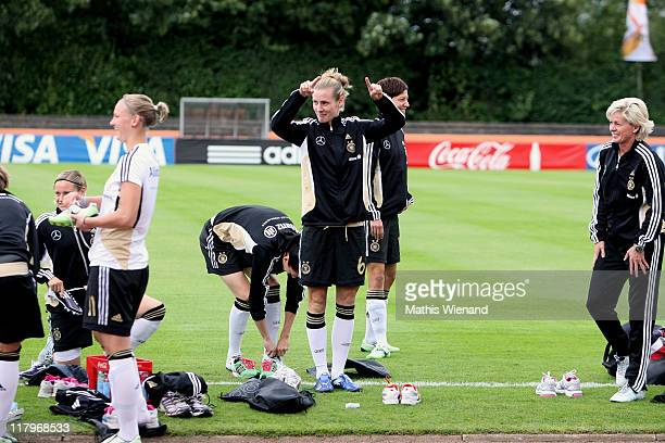 Simone Laudehr conducts the singing fans during the Germany Women national team training session at Eisenbrand stadium on June 21 2011 in...