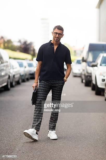 Simone Marchetti exits the Salvatore Ferragamo show in Valentino Alexander McQueen shoes and an Officina Del Poggio clutch on June 21 2015 in Milan...