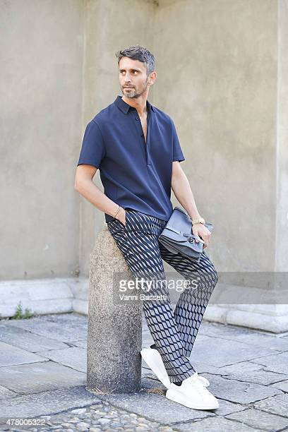 Simone Marchetti poses wearing Valentino shirt and trousers ODP bag and McQueen shoes on June 21 2015 in Milan Italy