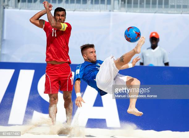 Simone Marinai of Italy attempts a scissor kick shot on goal in front Mohammad Ahmadzadeh of Iran during the FIFA Beach Soccer World Cup Bahamas 2017...