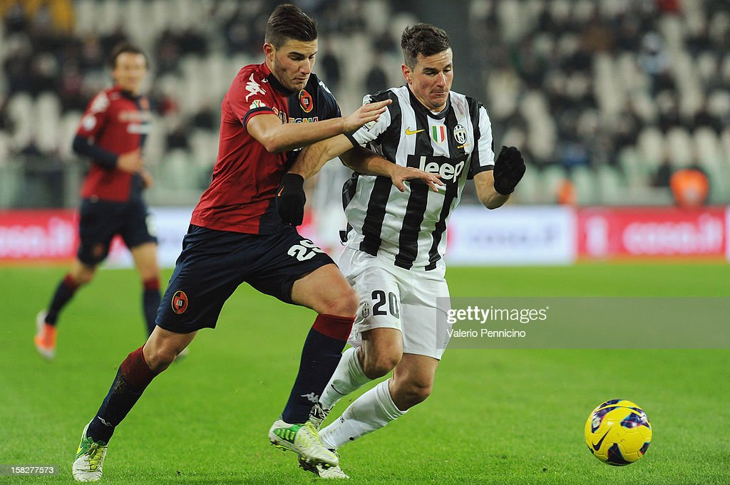 Simone Padoin (R) of Juventus FC is challenged by Nicola Murru of Cagliari Calcio during the TIM Cup match between Juventus FC and Cagliari Calcio at Juventus Arena on December 12, 2012 in Turin, Italy.