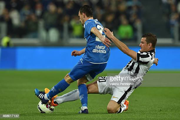 Simone Padoin of Juventus FC tackles Mario Rui of Empoli FC during the Serie A match between Juventus FC and Empoli FC at Juventus Arena on April 4...