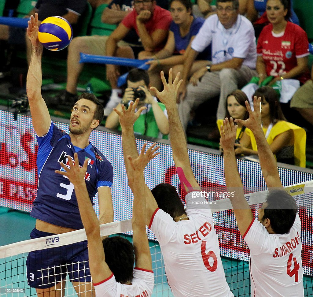 Simone Parodi of Italy spikes the ball as Iran players block during the FIVB World League Final Six match for the third place between Iran and Italy at Mandela Forum on July 20, 2014 in Florence, Italy.