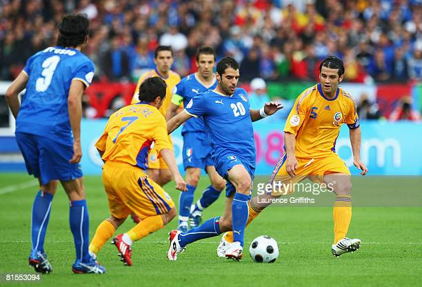 Simone Perrotta of Italy is challenged by Florentin Petre and Cristian Chivu of Romania during the UEFA EURO 2008 Group C match between Italy and...
