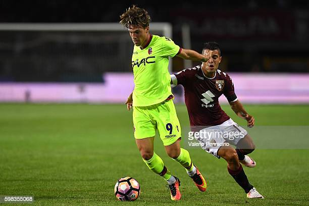 Simone Verdi of Bologna FC is challenged by Iago Falque of FC Torino during the Serie A match between FC Torino and Bologna FC at Stadio Olimpico di...