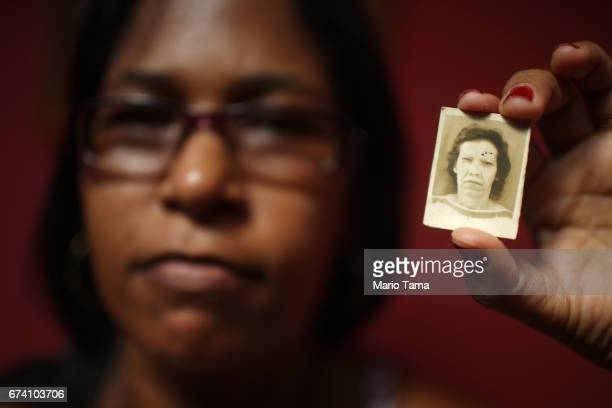 Simone Vieira da Rocha de Lucena poses with a photo of her mother on April 21 2015 in São Gonçalo Brazil