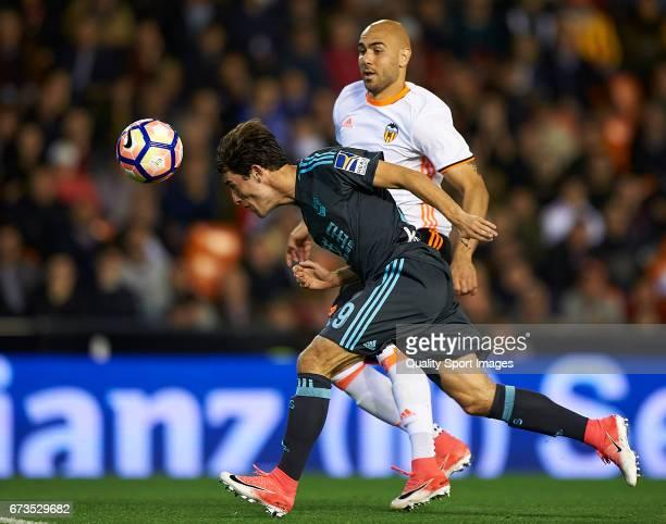 Simone Zaza of Valencia competes for the ball with Alvaro Odriozola during the La Liga match between Valencia CF and Real Sociedad de Futbol at...