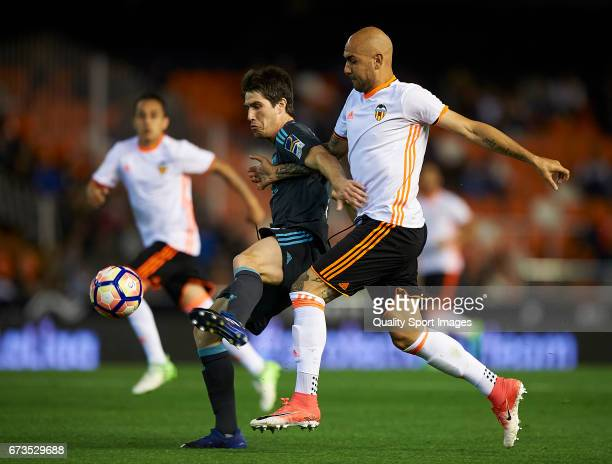 Simone Zaza of Valencia competes for the ball with Aritz Elustondo of Real Sociedad during the La Liga match between Valencia CF and Real Sociedad de...