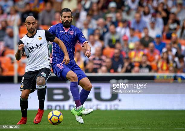 Simone Zaza of Valencia competes for the ball with Dimitrios Siovas of Leganes during the La Liga match between Valencia and Leganes at Mestalla...