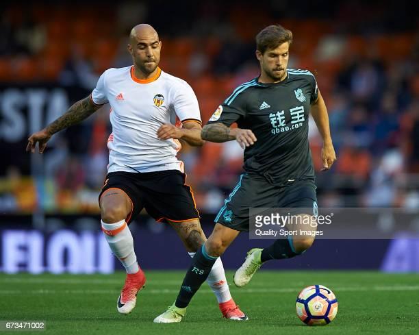 Simone Zaza of Valencia competes for the ball with Inigo Martinez of Real Sociedad during the La Liga match between Valencia CF and Real Sociedad de...