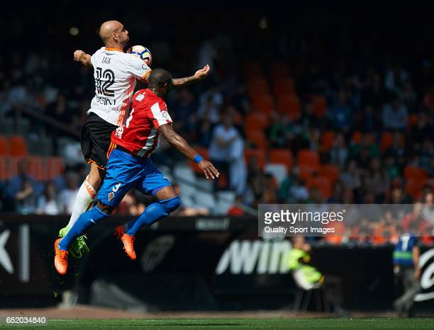 Simone Zaza of Valencia competes for the ball with Jean Sylvain Babin of Real Sporting de Gijon during the La Liga match between Valencia CF and Real...