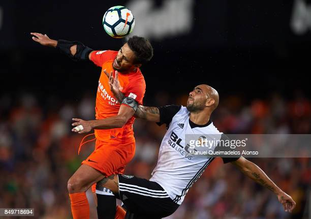 Simone Zaza of Valencia competes for the ball with Jose Luis Garcia Recio of Malaga during the La Liga match between Valencia and Malaga at Estadio...