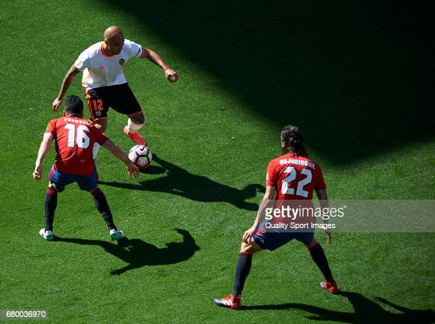 Simone Zaza of Valencia competes for the ball with Juan Rafael Fuentes and Nikola Vujadinovic of Osasuna during the La Liga match between Valencia CF...