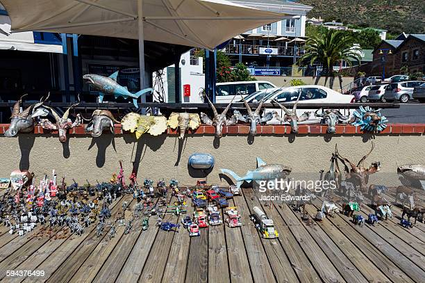 An artist displays his metal sculptures made from car parts on a jetty.