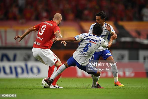 Simovic of Nagoya Grampus keeps the ball while Jungya Kim and Yosuke Ideguchi of Gamba Osaka challenge the ball during the J League match between...