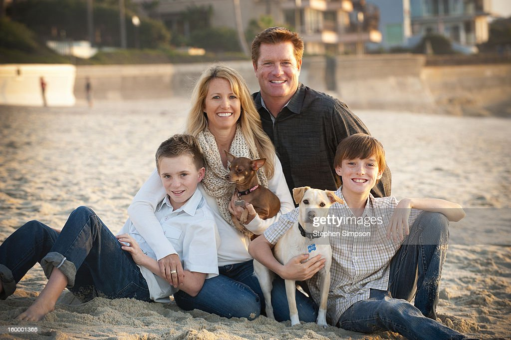 simple family portrait on the beach, with dogs : Stock Photo